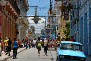 Gadebillede i Havanna med mennesker og en blå bil