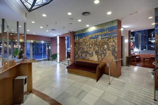 Lobby med sofa, gråt flisegulv og billede på væggen