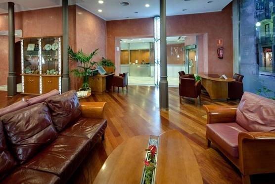 Lobby i hotel med lædersofaer, søjler, træbord og planter