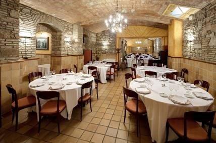 Flere borde med hvide duge og stole og en lysekrone i en restaurant