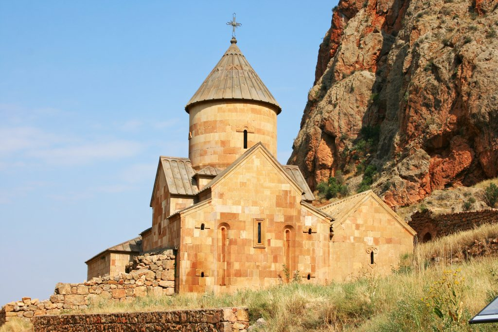 Kloster i brune mursten med klipper bag og græs omkring