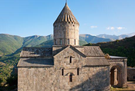 Kloster med tårn og grønne bakker i baggrunden
