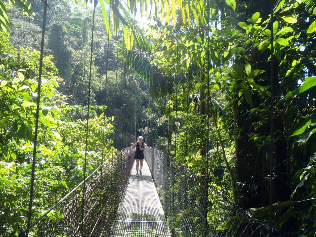 Kvinde på hængebro i regnskoven i Costa Rica