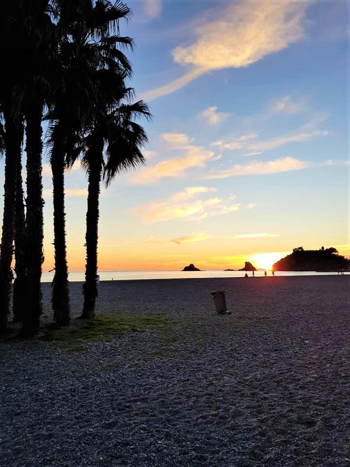 Solnedgang på strand med palmer i Sydspanien