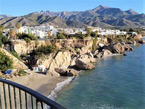 Strand omgivet af klipper med by i baggrunden