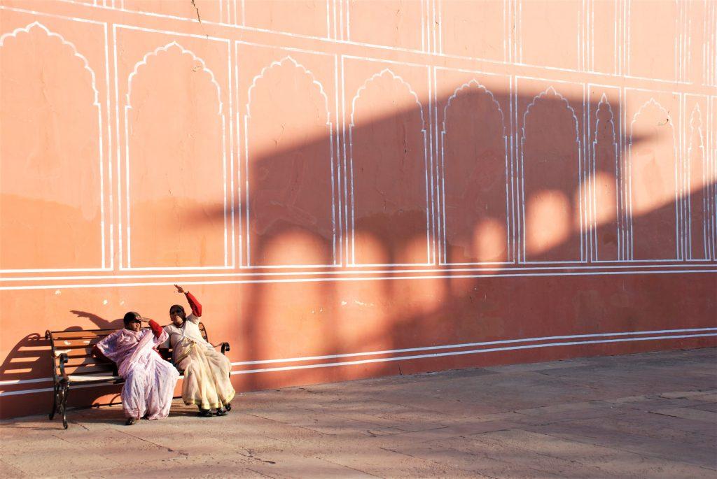 To kvinder i Indien sidder på en bænk med en rød mur bagved