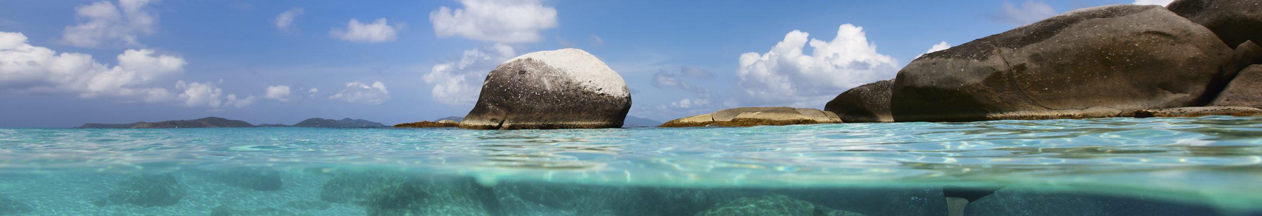 Dykker under havoverfladen i krystalklart vand med klipper i baggrunden